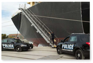 Two police cars parked in front of a large ship