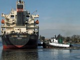 A cargo ship being moved by tugboats