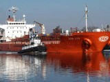 A tugboat towing a red cargo ship through the river.