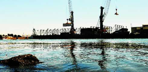 "Crane operators at the Port of Stockton load containers onto a barge that will take them down the ""Marine Highway."""