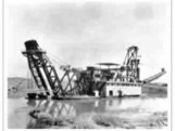 A old picture of a dredging boat in the river.
