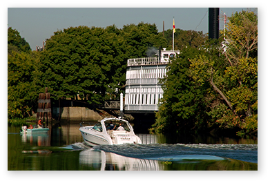 Motor boat and fishing boat passing ferry on the river