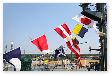 Multiple nautical flags strung up on a ship.