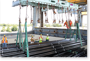 Workers unloading long metal pipes with a port crane.