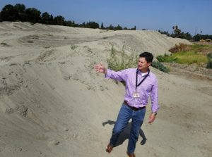 The Port of Stockton's Jeff Wingfield stands atop a mountain of sand and sediment at Rough and Ready Island dredged from the channel - about 200,000 cubic yards, enough to fill a line of dump trucks stretching from Stockton to Oakland.