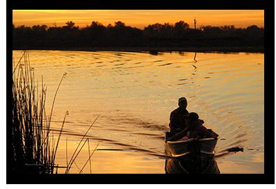 Small boat motoring at sunset