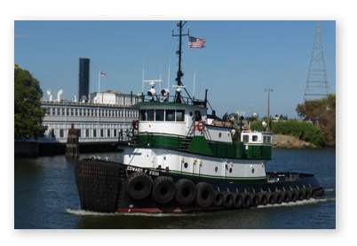 A green and white tugboat moving through the channel.