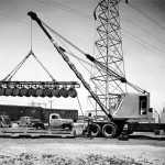 Old picture of a crane loading barrels onto a pallet.
