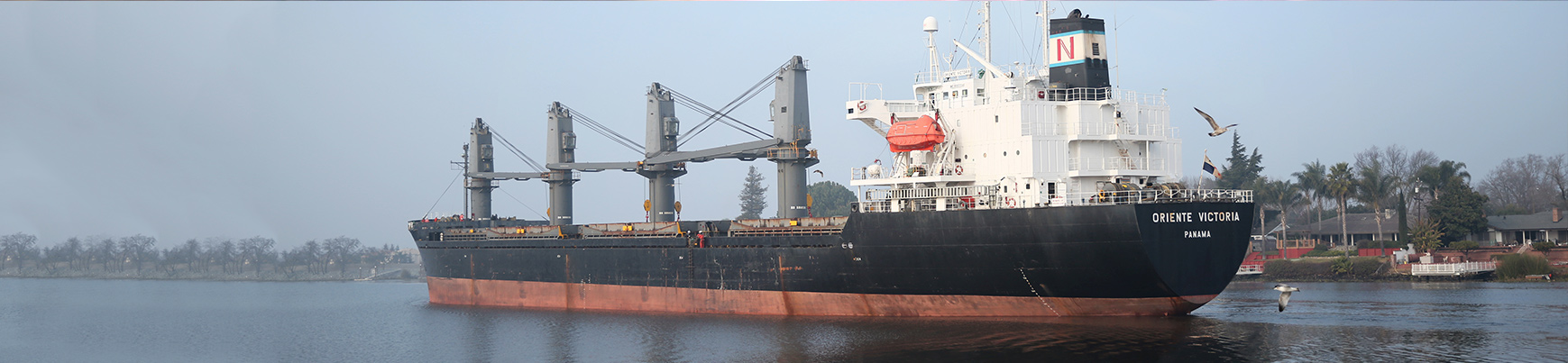 Large cargo ship sailing through river
